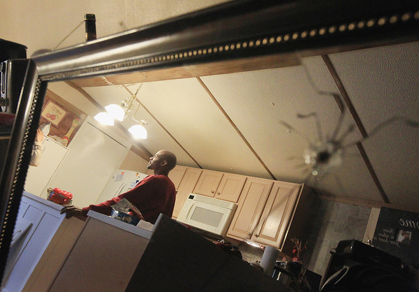 Record-Eagle/Keith King<br /> Damage from a bullet is visible on a mirror Monday, April 8, 2013 as Lance Reed, of Grawn, describes the incident in which a bullet was fired toward his home.