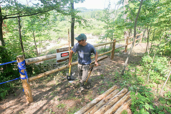 Record-Eagle/Keith King<br /> Tom Vitale, Grand Traverse Conservation District parklands specialist, carries tools to work on a fence as part of a trail-rerouting project, due to eroding banks, along the Boardman River near the Lone Pine Trailhead in Grand Traverse County.