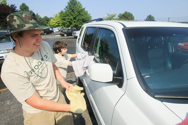 Record-Eagle/Keith King<br /> River Leachman, left, 14, and Peter Beard, 13, both with Boys Scouts of America Troop 31, along with their fellow scouts, wash cars as a part of the Kelsey Clous fundraiser at Bill Marsh Auto Group in Traverse City. A silent auction, bake sale, a portion of proceeds from oil changes and lunch also took place during the fundraiser.