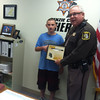 Record-Eagle/Glenn Puit<br /> Logan Snyder receives an award for heroism from Benzie County Sheriff Ted Schendel.