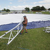 Record-Eagle/Keith King<br /> Nick Gallivan, of G.J.'s Rentals, moves a section of frame Wednesday, August 14, 2013 as he and other workers assemble a SaddleSpan tent at the Open Space for Paella in the Park, scheduled for Friday, and the Great Lakes Festival, scheduled for Saturday.