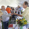 Record-Eagle/Keith King<br /> Lyn Parmenter, from left, of Traverse City, stands near as Steve Nowak, of Traverse City, receives a glass of Boathouse Vineyards wine from Skip Pruss Saturday, August 10, 2013 during the Northport Wine Festival.