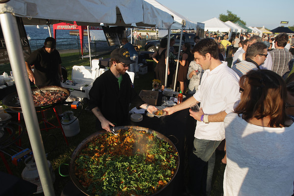 Record-Eagle/Keith King<br /> Cody Patterson, with Black Star Farms, serves vegetarian paella, with arugula and wild mushrooms, to Ryan Hughes, of Traverse City, Friday, August 16, 2013 during Paella in the Park at the Open Space.