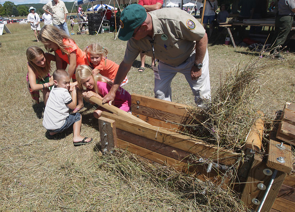 Record-Eagle/Keith King<br /> Jessa Vandenberg, from left, 11, Morgan Austin, 8, Sam Austin, 5, Allie Vandenberg, 9 and Kate Vandenberg, 6, all of Rockford, along with Sleeping Bear Dunes National Lakeshore volunteer, J.D. Fasnaugh, operate a hay baler by hand Saturday, August 10, 2013 during the annual Port Oneida Fair.