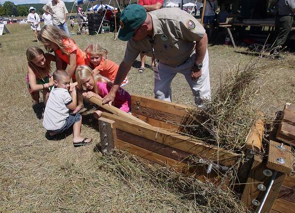 Record-Eagle/Keith King<br /> From left, Jessa Vandenberg, 11; Morgan Austin, 8; Sam Austin, 5; Allie Vandenberg, 9; and Kate Vandenberg, 6, all of Rockford, along with Sleeping Bear Dunes National Lakeshore volunteer, J.D. Fasnaugh, operate a hay baler by hand Saturday, August 10, 2013, during the annual Port Oneida Fair.