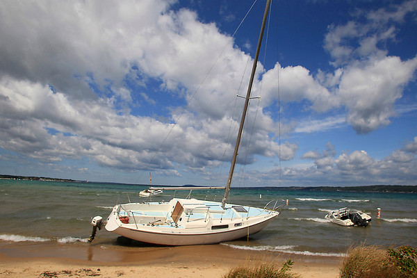 Record-Eagle/Jan-Michael Stump<br /> A sailboat and powerboat sit beached at West End Beach on Saturday afternoon, some of the several boats swamped or beached along the southern end of West Grand Traverse Bay following Friday's strong winds.