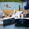 Blessed by summer<br /> Record-Eagle/Dan Nielsen<br /> Swimmers frolic in the bay near a sailboat named Blessed in the Suttons Bay Marina.