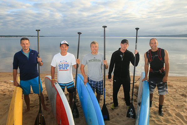 Record-Eagle/Keith King Andrew Pritchard, from left, Kwin Morris, Jeff Guy, Joe Lorenz and Joel Mueller stand at West Grand Traverse Bay. The group are planning to travel on Lake Michigan, using stand-up paddleboards, from Algoma, Wisconsin to Frankfort, Michigan to raise money for Alliance for the Great Lakes.