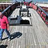 Record-Eagle/Nathan Payne<br /> Randy McClure walks across the deck of the Welcome, a 55-foot-long, armed sloop owned by the Maritime Heritage Alliance. Two cranes will hoist the boat from the water Tuesday and place it on a truck destined for Emmet County.