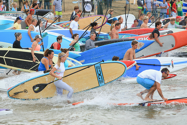 Record-Eagle/Keith King Stand-up-paddle boards are carried by racers into West Grand Traverse Bay during the TC Waterman Challenge and Expo in Traverse City.