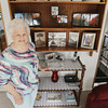 Record-Eagle/Keith King<br /> Shirley Rogers, of Traverse City, stands Wednesday, August 14, 2013 in her home near a collection of books relating to the Traverse City State Hospital, where she worked for 31 and a half years until it closed in 1989. Rogers organizes reunions for employees that worked at the hospital.