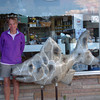 Traverse City Record-Eagle/Marta Hepler Drahos<br /> Donna Ervin stands with Rock Bass, a 5 1/2-foot fish painted to look like a Petoskey stone, outside her Glenwood Market in downtown Frankfort.