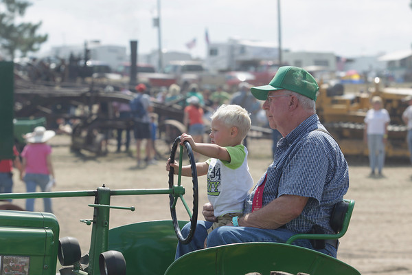 Record-Eagle/Keith King<br /> Ron Cade, of Otsego, and his nephew, Keaton Cade, 2, of Buckley, sit on Ron's 1951 John Deere A tractor as they wait in line during the Big Parade of All Vehicles Saturday, August 17, 2013 during the 46th annual Buckley Old Engine Show.