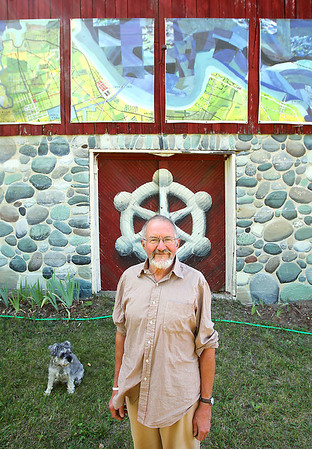 "Record-Eagle/Keith King<br /> Jerry Gretzinger, of Maple City, with his dog Bubba nearby, stands Tuesday, August 21, 2012 near some enlargements on his barn (the originals being eight inches by ten inches ) of his work which represent a small portion of his project titled, ""Jerry's Map."" The project is scheduled to be shown at the Massachusettes Museum of Contemporary Art."