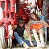Record-Eagle/Jan-Michael Stump<br /> Calvin Willford, of Gladwin, and Sydney Pylman, of Evart, relax in the shade next to a 1927 Farmall F-12 owned by Pylman's uncle, Michael Pylman.