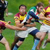 Record-Eagle/Jan-Michael Stump<br /> Traverse City Blues'  Champ Bodell runs past a pair of CMU players Saturday during the Cherry Pit Rugby Tournament.