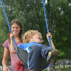 Lindsay Steele/ Record-Eagle<br /> Henry Sutherland, 4, squeals for joy as his mother Amy Sutherland pushes him on the swings Tuesday at Suttons Bay Marina Park.