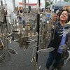 Record-Eagle/Keith King<br /> Suzanne Howell, of Burton, looks at wind chimes made by Ron Egelski, of Alpena, during the Downtown Art Fair in Traverse City.