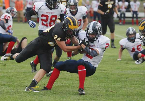 Record-Eagle/Keith King<br /> Glen Lake's David Grzebienik (24) tries to bring down Boyne City's Bradley Fouchia (2) Thursday, August 29, 2013 at Glen Lake Community Schools.