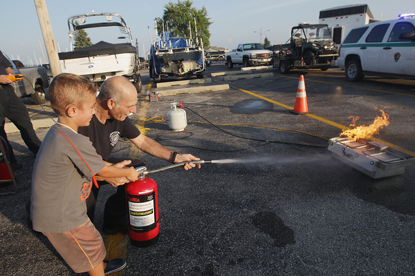 Record-Eagle/Keith King<br /> Jacob Gulley, 6, of Elmwood Township, is shown by Mike Wallman, Elmwood Township Fire and Rescue water supply officer, how to use a fire extinguisher Wednesday, August 28, 2013 during Leelanau County Public Safety Day and Fire Department Recruitment at Greilickville Harbor Park and Elmwood Township Marina.