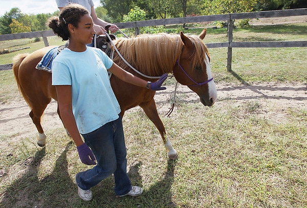 Record-Eagle/Keith King<br /> Volunteer Nikki Kaschel walks with a horse and rider in a round pen Tuesday, August 28, 2012 at the Professional Equine Assisted Counseling and Education (PEACE) Ranch in Blair Township.