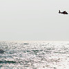 Record-Eagle/Keith King<br /> A United States Coast Guard helicopter flies overhead as a Leland Township Fire and Rescue boat travels on Lake Michigan Thursday, August 30, 2012 as the search for a missing swimmer takes place in Leland.