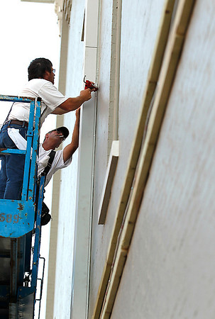 Record-Eagle/Jan-Michael Stump<br /> Ross O'Connor, front, and Brian Coates, of Comstock Construction, install pilasters on the Union Street side of a Front Street building Friday.