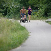 Record-Eagle/Jan-Michael Stump<br /> Brian and Abby Gartland run with their children, Scarlet, 2, and Brooks, 1, on the Boardman Lake Trail on Wednesday, near a stretch where officials are considering linking the trail on the west side of Boardman Lake to Airport Road.