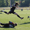 Record-Eagle/Jan-Michael Stump<br /> Leland's Dylan Jolliffe (13)  leaps over Traverse City Christian goalkeeper John Edingfield in the second half of Monday's game.