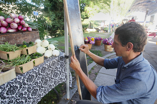 Record-Eagle/Keith King<br /> Nicolas Theisen, owner of Loma Farm, of Leelanau County, uses a chalkboard to write what is available for sale and prices Wednesday, August 7, 2013 during the Sara Hardy Downtown Farmers Market.