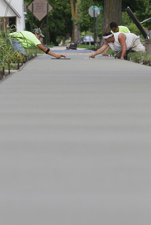 Record-Eagle/Keith King<br /> Mike Clark, from left, Gabe Lindsay and Jaime Rodriguez, with Hallmark Construction, finish a concrete sidewalk Wednesday, August 7, 2013 along Wadsworth Street in Traverse City.
