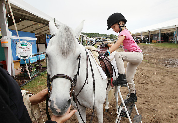 Record-Eagle/Keith King<br /> Ayla Downer, 6, gets on Riley, a pony, at the Northern Pines Farm area Wednesday, July 25, 2012 during the Horse Shows by the Bay Equestrian Festival at the Flintfields Horse Park in Acme Township.