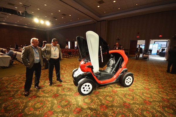 Record-Eagle/Dan Nielsen<br /> Attendees at the Center for Automotive Research Management Briefing Seminars ponder a small display vehicle inside Governor's Hall at the Grand Traverse Resort & Spa.