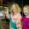 "Record-Eagle/Keith King<br /> Mairead Seyfarth, right, 8, of Traverse City, laughs as she holds hands with Kaitlin Cesario, 9, of Traverse City, who has her hand on a Van de Graaff electrostatic generator during Super Science Saturday hosted by Traverse City Central High School. ""When I held her hand I felt an electric force field around me,"" Seyfarth said."
