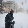 Record-Eagle/Keith King<br /> Jamie Al-Shamma, of Traverse City, sips coffee as he walks in heavy snowfall toward his vehicle so he can pick up his wife, son and daughter.