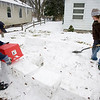 Record-Eagle/Keith King<br /> Dennis Phillips, left, of Traverse City, uses a plastic drawer to make blocks of snow as he and his son, Nathan, 10, make a snowball fort in front of their home, with plans of building a second one. The forts, built as part of an annual Christmas tradition, will be used when family members arrive from downstate for the holidays.