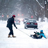 """Record-Eagle/Jan-Michael Stump<br /> Warren Call pulls his children Winston, 2, and Sofia, 6, on a sled down Wadsworth Street. """"We like going over the<br /> bumpies,"""" said Sofia, referring to the piles of snow created by snowplows."""