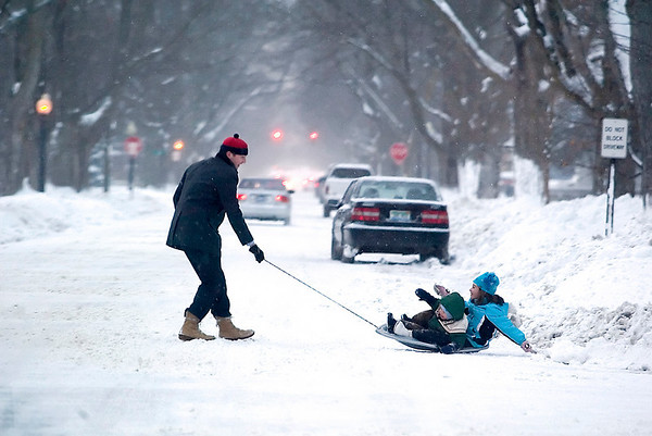 "Record-Eagle/Jan-Michael Stump<br /> Warren Call pulls his children Winston, 2, and Sofia, 6, on a sled down Wadsworth Street. ""We like going over the<br /> bumpies,"" said Sofia, referring to the piles of snow created by snowplows."