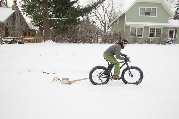 Record-Eagle/Keith King<br /> Ty Schmidt, of Traverse City, demonstrates Tuesday a snow plow he pulls behind a bicycle.