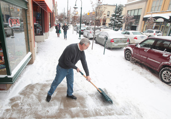 Record-Eagle/Keith King<br /> Bob Long, manager, shovels snow in front of Trains and Things Hobbies as snow accumulates Friday in downtown Traverse City.