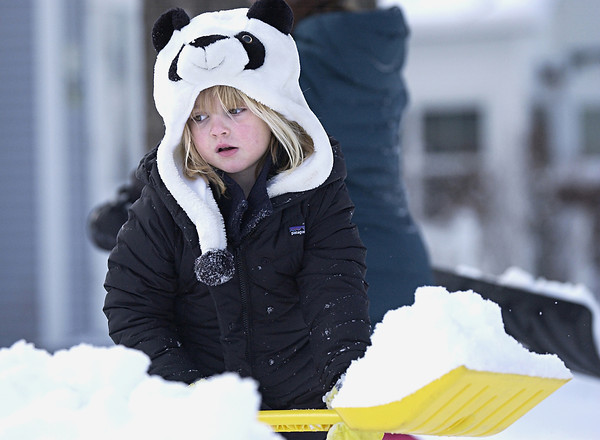 "Record-Eagle/Nathan Payne<br /> Molly Desmond, 5, lugs a shovel full of snow to a fort in her front yard in downtown Traverse City on Monday afternoon while she and her two sisters worked to make a fort. The trio spent most of the afternoon playing outside during the first snowday of the school year. About six inches of powdery snow blanketed most of the region Monday morning after a cold front pushed through the area. The snow was abundant, but not the perfect kind for packing. ""I wish it was a little warmer so it would pack,"" said Julie Hearne, the girls' mother."