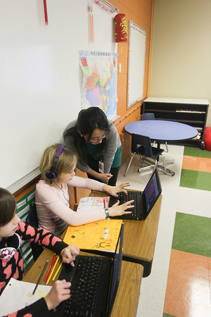 Record-Eagle/Keith King<br /> Yiling Liu, from China, helps Sage Brown, student, Wednesday in her class at Traverse City Area Public Schools (TCAPS) International School at Bertha Vos in Williamsburg.