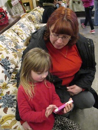 Laura Zann waits to shop for Christmas gifts at the Father Fred Foundation with her 4 1/2 year old daughter, who is playing with a borrowed cell phone.