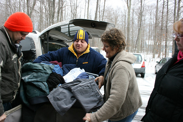 Record-Eagle/Loraine Anderson<br /> Volunteer Debbra Maidens helpsJoshua Ullum in blue jacket and Charles Esser empty a basket of clothing in the Benzie Area Christian Neighbors.  Priscilla Esser, far right, is also pictured.