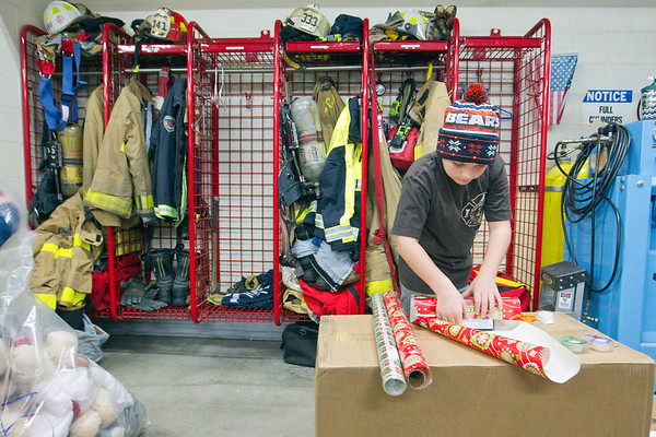 Record-Eagle/Jan-Michael Stump<br /> Caleb Chinlund, 10, wraps presents inside Fire Station 1 with the Traverse City Fire Department and over 40 volunteers on Saturday morning. The annual tradition, which will help about 200 children from Grand Traverse County this Christmas, dates back to the late 1940s when firefighters would repair toys for local children in need. The program now collects donations from local businesses, schools and community members, as well as from Toys for Tots.