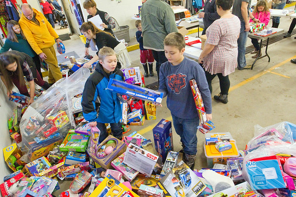 Record-Eagle/Jan-Michael Stump<br /> Jack Tafelski, 7, left, and his brother Marcus Tafelski, 10, select presents for a child's wish list inside Fire Station 1 with the Traverse City Fire Department and over 40 volunteers on Saturday morning. The annual tradition, which will help about 200 children from Grand Traverse County this Christmas, dates back to the late 1940s when firefighters would repair toys for local children in need. The program now collects donations from local businesses, schools and community members, as well as from Toys for Tots.