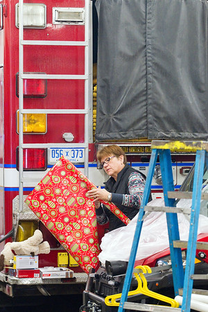 Record-Eagle/Jan-Michael Stump<br /> Karen Britto wraps a present next to a fire truck as members of the Traverse City Fire Department and over 40 volunteers wrap presents inside Fire Station 1 on Saturday morning. The annual tradition, which will help about 200 children from Grand Traverse County this Christmas, dates back to the late 1940s when firefighters would repair toys for local children in need. The program now collects donations from local businesses, schools and community members, as well as from Toys for Tots.