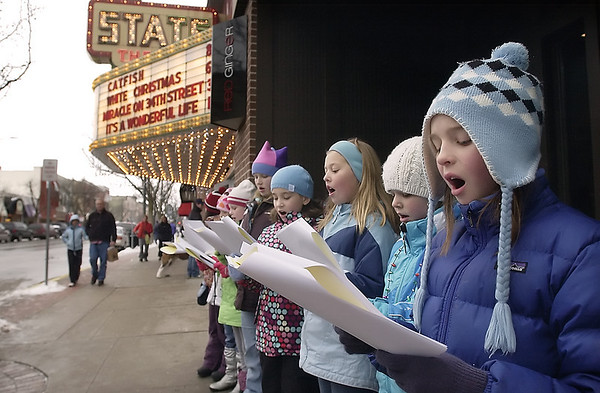 Record-Eagle/Garret Leiva<br /> Grace Argyle, 10, second from right, sings Christmas carols with her friends Sunday outside of Red Ginger on Front Street in Traverse City. Argyle recruited several fifth-grade friends from Eastern Elementary to help her with a singing fundraiser to benefit Love Inc. and the Humane Society this holiday season.
