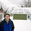 Record-Eagle/Keith King<br /> Jim Barnes, a solar contractor at Eco-Building Products, stands next to a garage in Traverse City where he installed a roof-mounted photovoltaic system.