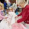 Record-Eagle/Keith King<br /> Penny Lautner, right, of Traverse City, and her granddaughter, Sydney Frederick, 7, of Traverse City, wrap gifts and fill out gift tags Saturday alongside other volunteers at the Traverse City Fire Department Fire Station No. 1. The gifts will go to children in the community.